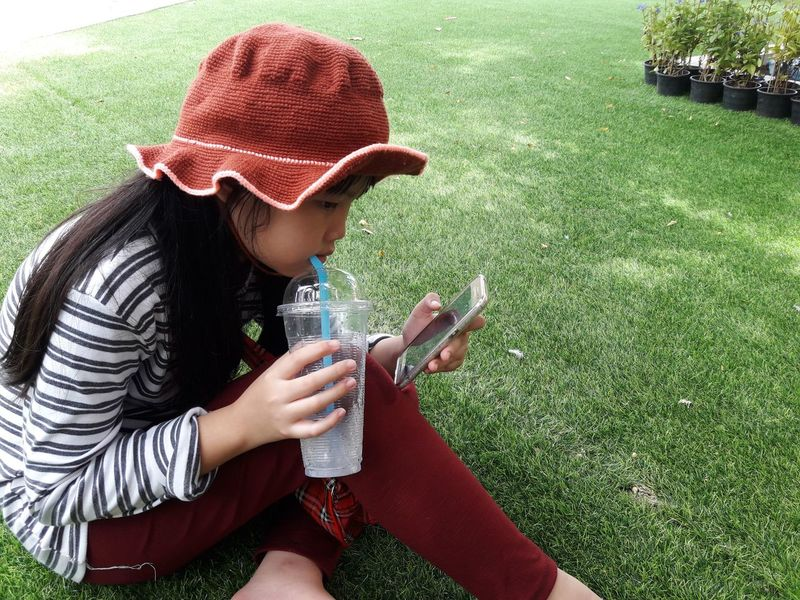 relaxing and happy girl Lifestyles Comfortable Feeling Girlholdingphone Asian Girl 8-9 Years Longhairgirl Child Childhood Rest Take A Rest Relaxgirl Greengrass Happygirl Playing Mobile Phone During Vacation Girl Drinking Water Holding Mobile Phone Women Drinking Glass Sitting Grass Casual Clothing