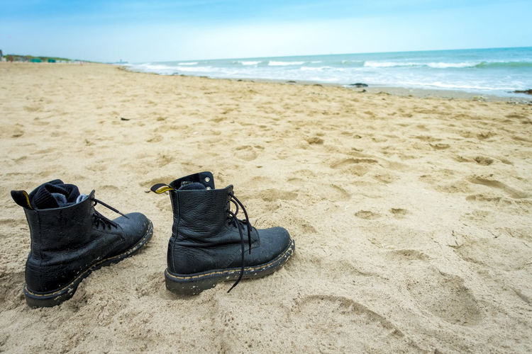 pair of boots at beach Boots Beach Beauty In Nature Close-up Day Horizon Over Water Nature No People Outdoors Pair Pair Of Boots Sand Scenics Sea Shoe Sky Water