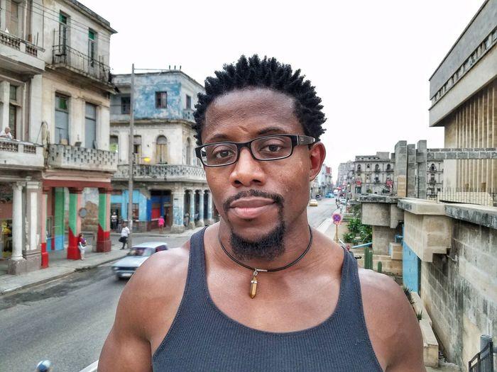 Portrait Of Man Wearing Eyeglasses Against Street In City
