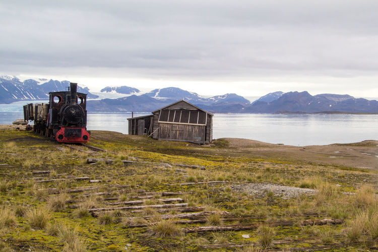 An old coal train in an abandoned settlement in Ny-Alesund, Svalbard in the arctic Transportation Mode Of Transportation Sky Train Cloud - Sky Rail Transportation Nature Mountain No People Day Land Vehicle Scenics - Nature Travel Beauty In Nature Outdoors Ny-Ålesund Coal Coal Train Abandoned Svalbard  Arctic Spitsbergen