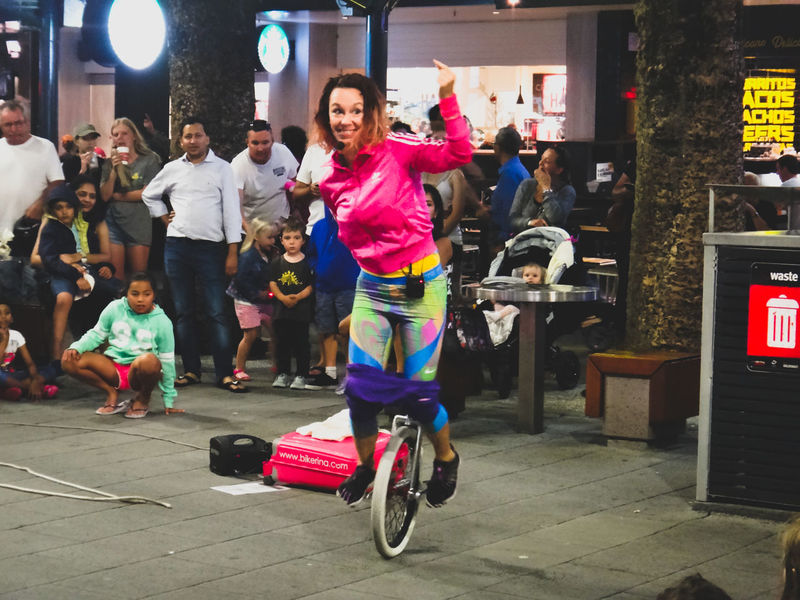 young woman doing a street act with a unicycle Adult City Crowd Full Length Fun Headwear Large Group Of People Leisure Activity Men Night Outdoors People Performer  Real People Street Entertainment Street Show Unicycle Women Young Adult Young Women Women Around The World Millennial Pink