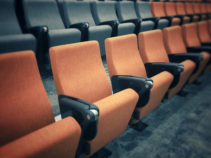 EyeEm Selects Row of empty seats. Chair Seat In A Row Arts Culture And Entertainment Indoors  Empty No People Emptiness Selective Focus Colour Orange Grey Empty Seats