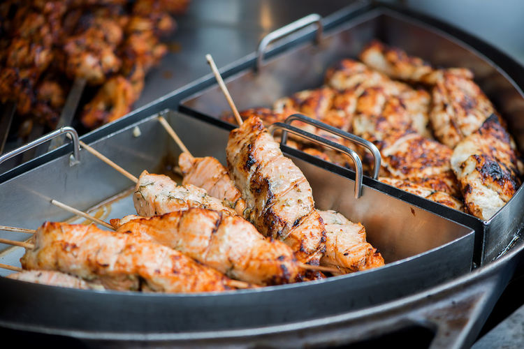 Close-up of barbecue meat in skewers on container