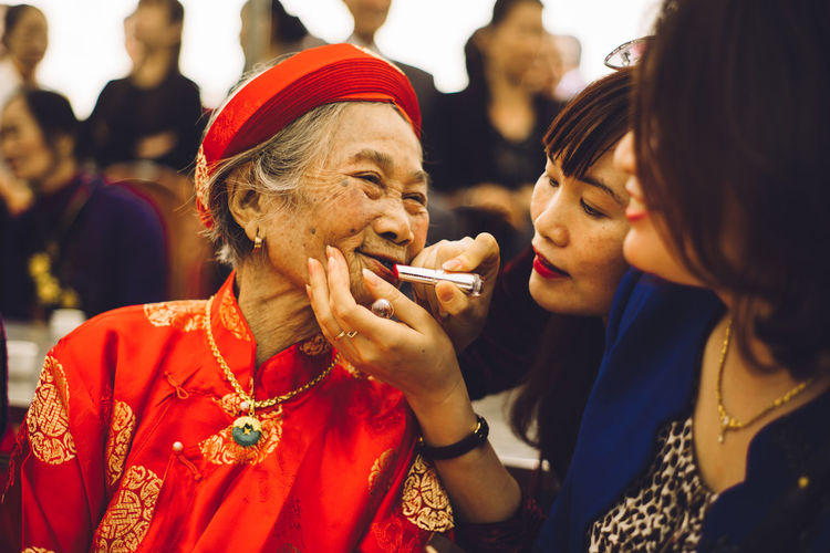 Close-up of woman applying lipstick on mother lips