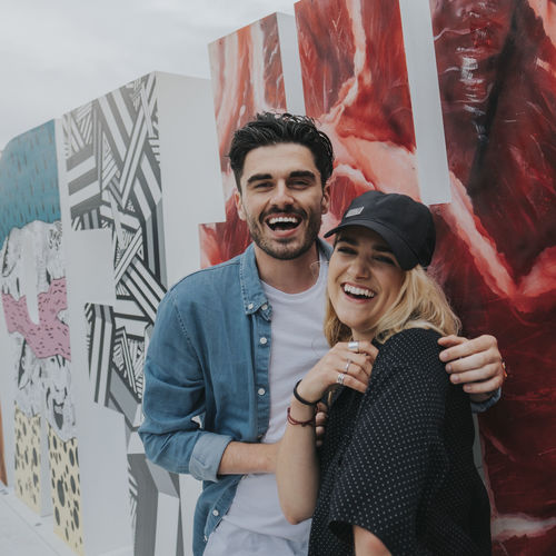 Portrait Of Smiling Young Couple Standing Outdoors