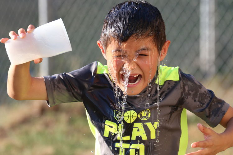 Boy pouring water over himself