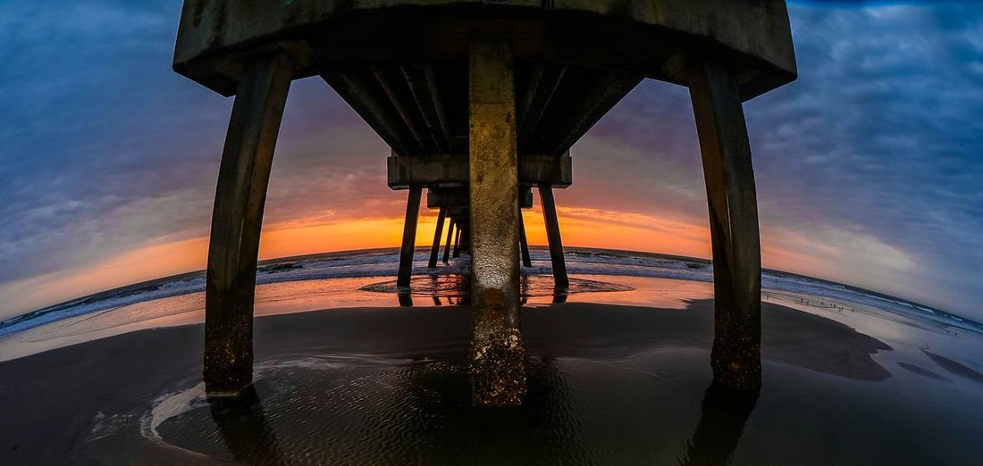Low angle view of pier on sea during sunset