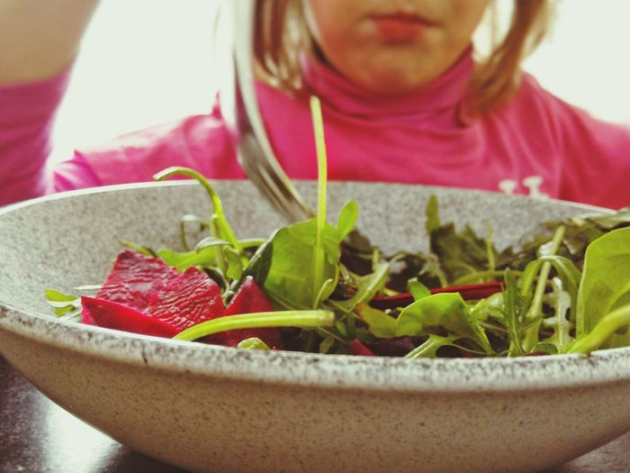 Close-up of salad in bowl with girl in background