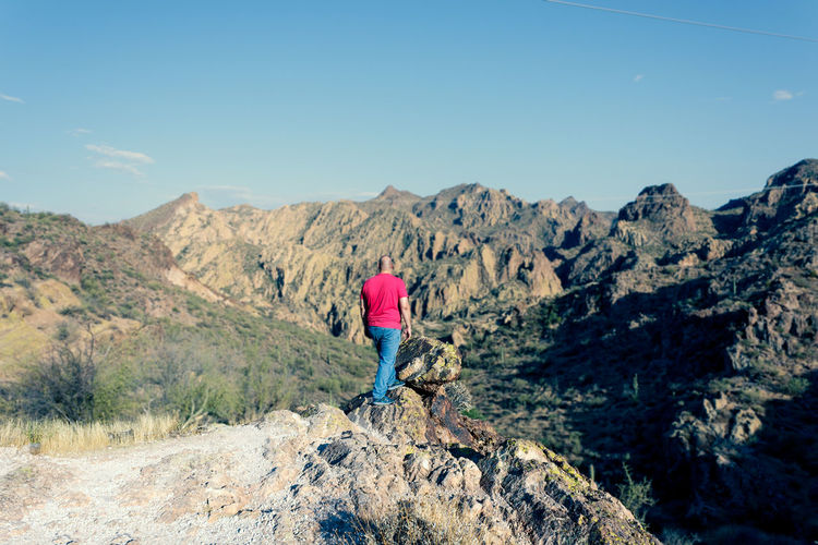 Rear view of hiker standing on rock against sky