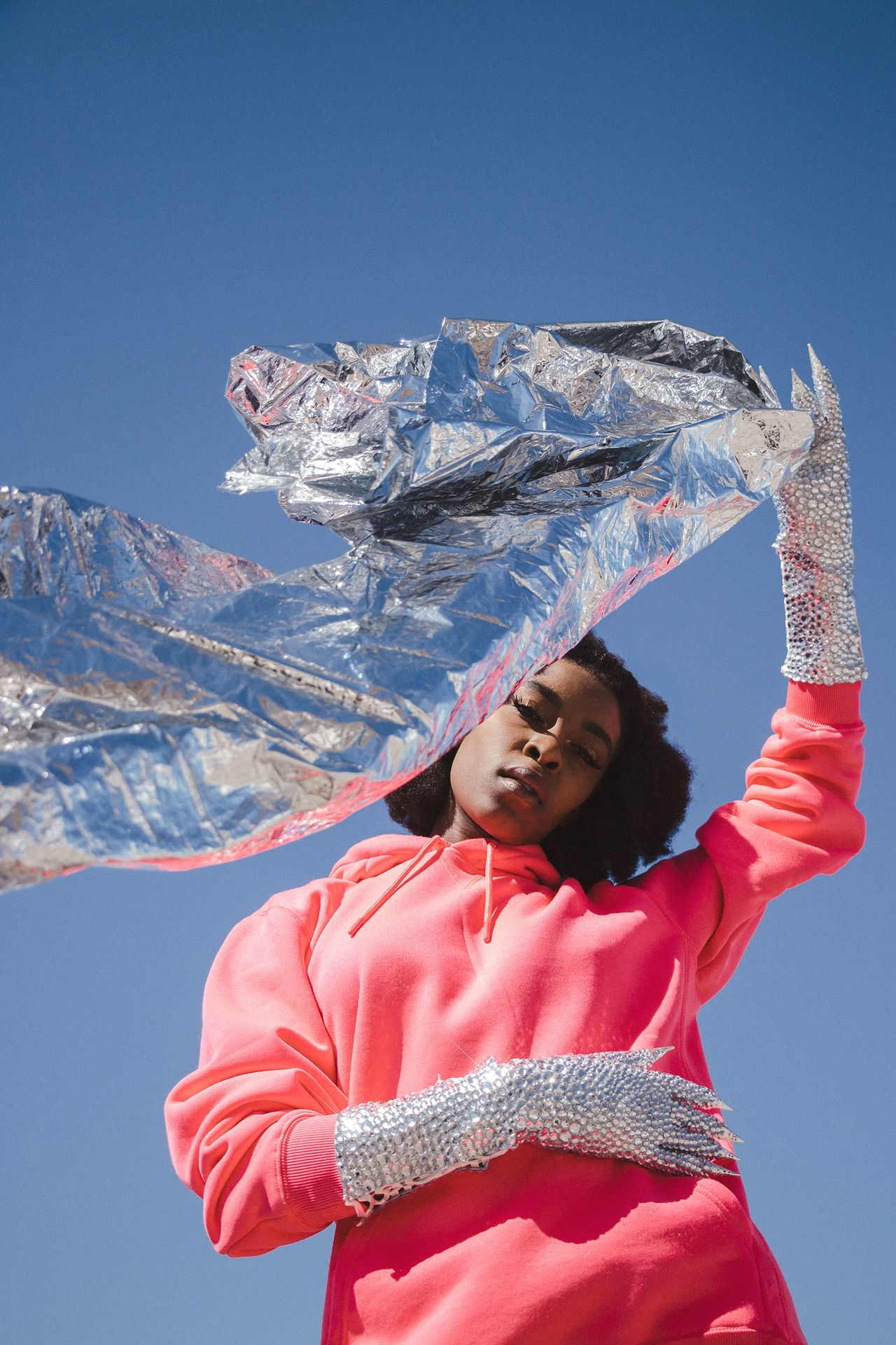 Low angle portrait of woman holding foil while standing against sky