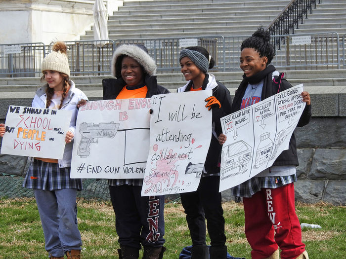 Students hold protest signs at the National School Walkout on the National Mall in front of the US Capitol building, Washington, DC, to demand political action to address gun violence on March 14, 2018. Activists National School Walk Out US Capitol Building Activism Building Exterior Casual Clothing Communication Day Grass Gun Control Gun Violence High School Students Holding Outdoors Paper People Placard Protesters Protestor Real People Teamwork Text Togetherness Young Adult