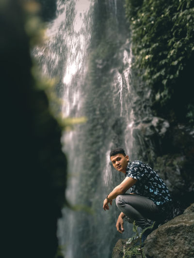 Full length portrait of young on on rock with waterfall in the background