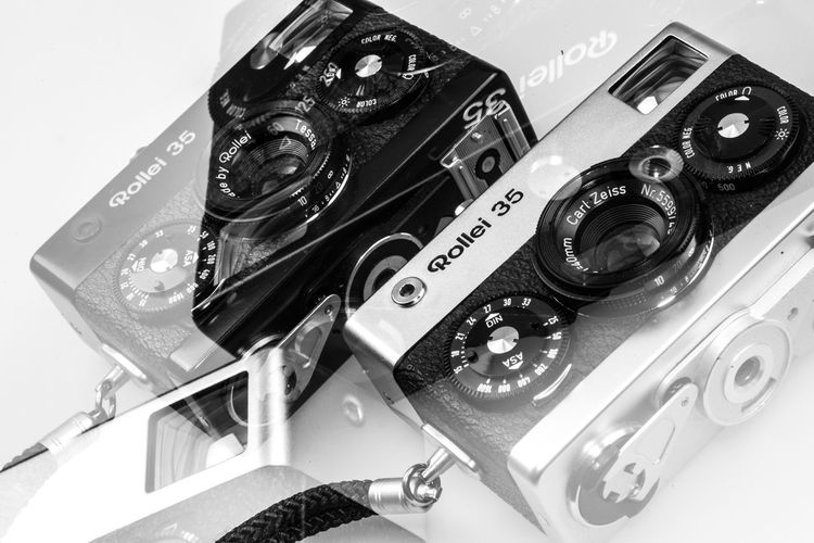Rollei 35 double exposure Close-up Still Life Photography Themes Technology Camera - Photographic Equipment Indoors  No People Photographic Equipment Retro Styled Arts Culture And Entertainment Film Industry High Angle View Camera Number Studio Shot Camera Film Table White Background Digital Camera