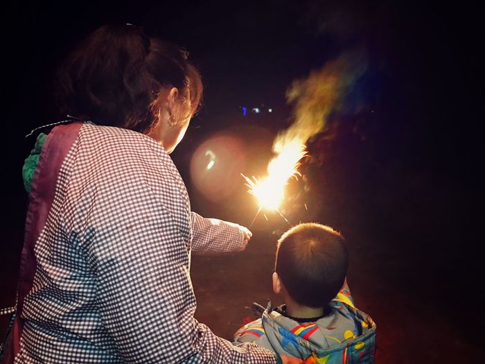 Adult Baby Bonding Celebration Chinese New Year Dark Dark And Light Dark Photography Darkness And Light Family Family With One Child Firework Firework Display IPhoneography Lifestyles Males  Mother Night Outdoors People Rear View Son Togetherness The City Light Focus On The Story
