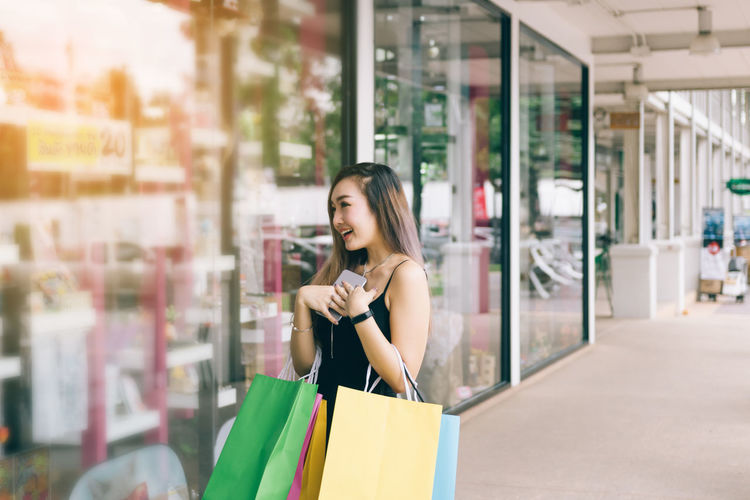 Young woman with shopping bags standing outside store