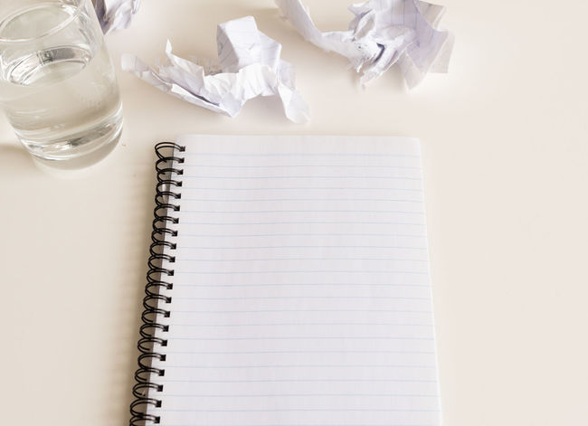 Blank notebook with glass of water Blank Book Copy Space Crumpled Crumpled Paper Crumpled Paper Ball Document Glass High Angle View Indoors  Message No People Note Pad Office Page Paper Pen Publication Spiral Notebook Still Life Studio Shot Table White Color