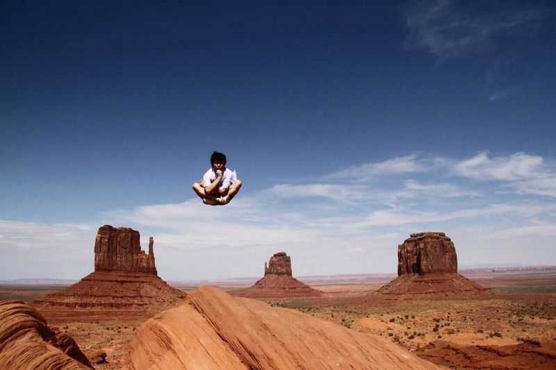 Man With Cross-Legged Levitating Over Rock Formation At Monument Valley Against Sky