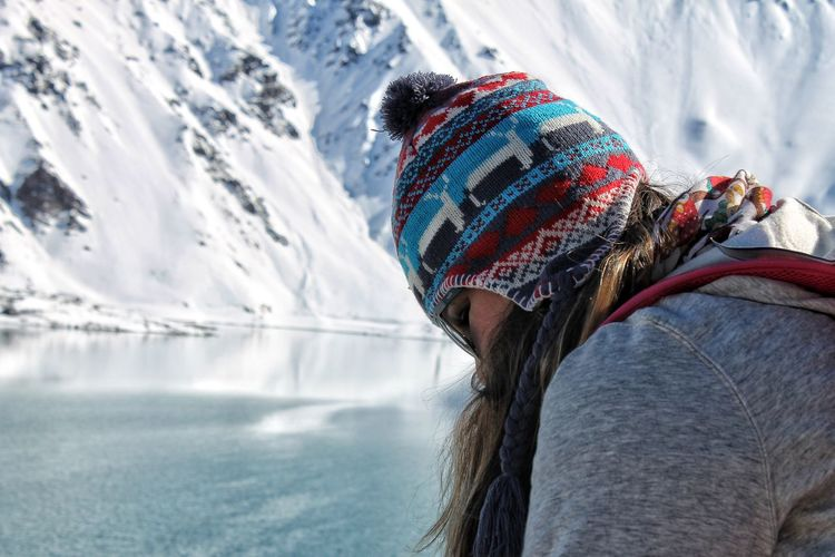 Woman wearing hat during winter against snowcapped mountain