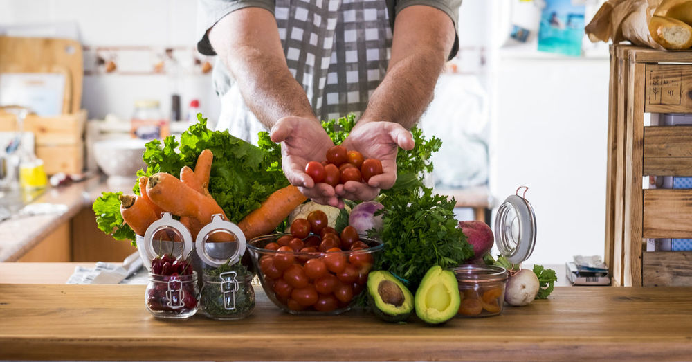 Vegetarian and healthy food lifestyle at home concept - table in the kitchen full of mixed coloured vegetables and man hands showing you the freshness - background and energy infredients to cook Food Food And Drink Vegetable Healthy Eating Wellbeing One Person Freshness Indoors  Fruit Domestic Kitchen Home Kitchen Domestic Room Midsection Domestic Life Lifestyles Preparation  Adult Choice Hand Preparing Food Avocado Arm Botany Bright Dinner Eating Freshness People Salad Table Wood Apron Tomato Vegetarian Food 45-49 Years Jar Casual Clothing Chef Man