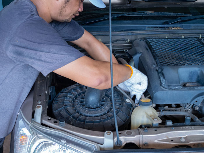 Mechanic holding a block wrench handle while fixing a car.