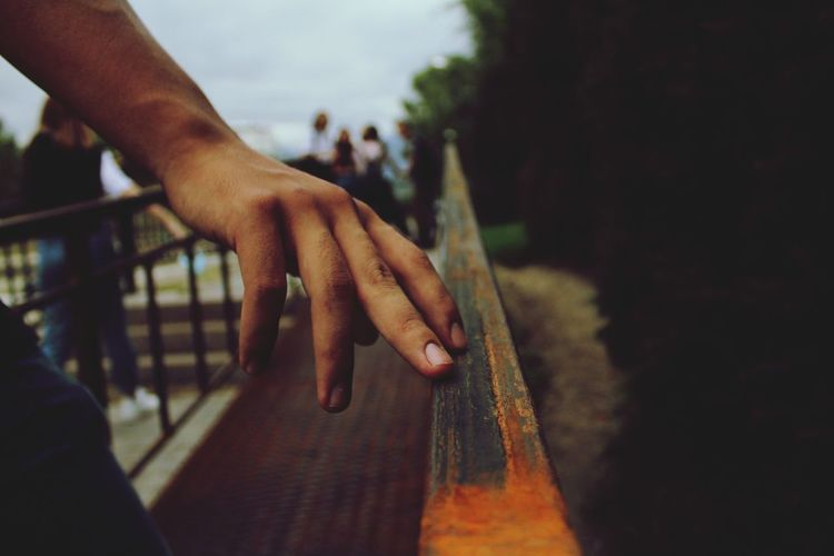 Close-up of hand touching railing