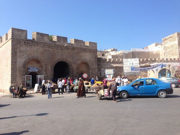 Arch Architecture Blue Building Exterior Built Structure City Clear Sky Copy Space Essaouira History Large Group Of People Marrocco Men Person Road Street Sunlight Transportation Travel Travel Destinations Walking