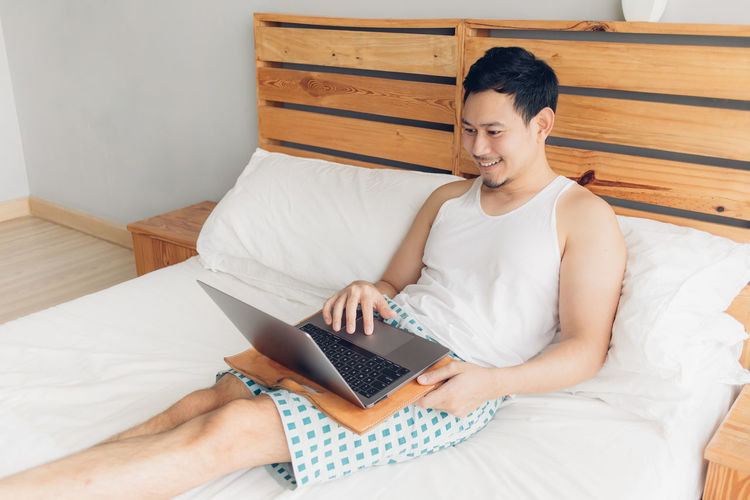 Young man using mobile phone while sitting on bed at home