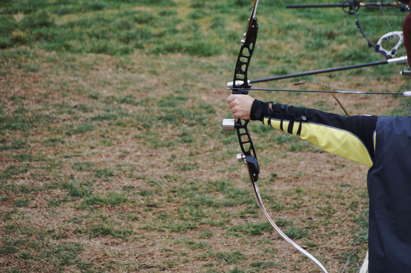 Archery Archery Bows Bow Bows Arrow Arrows Arrow - Bow And Arrow Shooting Target Target Shooting Holding One Person Land Nature Plant Field Sport Day Grass Leisure Activity Real People Focus On Foreground Outdoors Aiming Men Human Body Part Tree Adult Environment