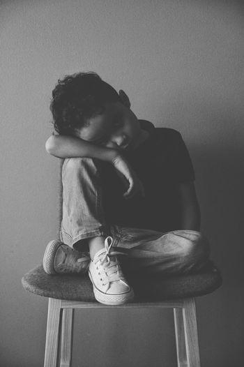 Portrait of sad boy sitting on chair against wall