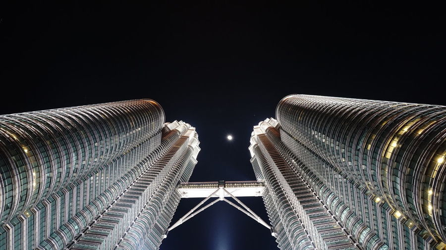 Low angle view of illuminated buildings against clear sky at night