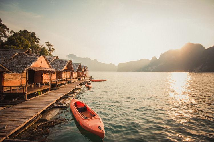 Canoe moored in lake during sunset