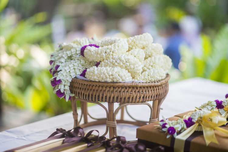 Close-up of white flowers in wicker basket on table during wedding