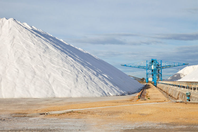 Large Heap Of Salt And Crane At Factory