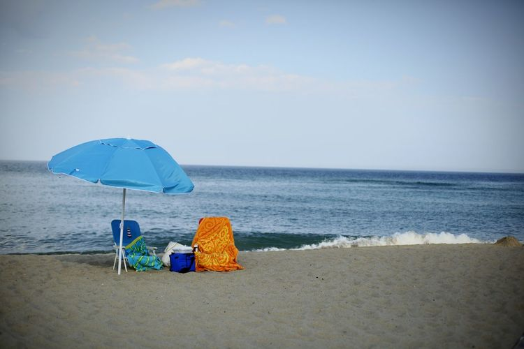 Chairs and umbrella at beach against sky