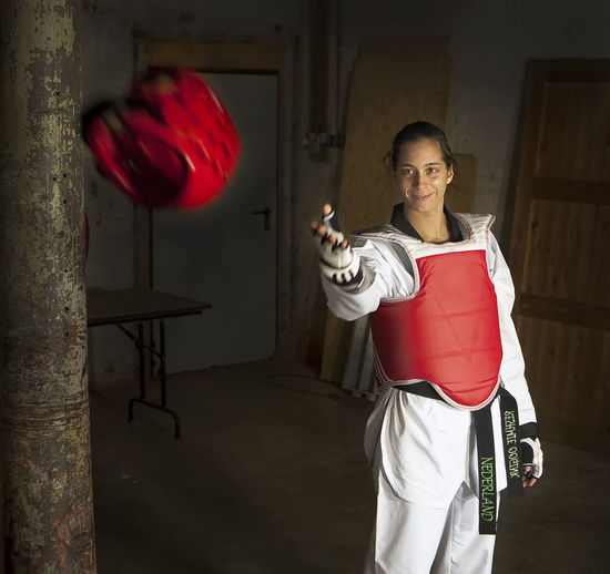 Smiling Woman Taekwondo Athlete Catching Red Head Protector