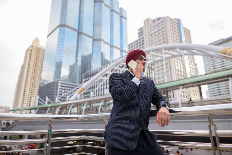 Full length of man standing on bridge against buildings in city