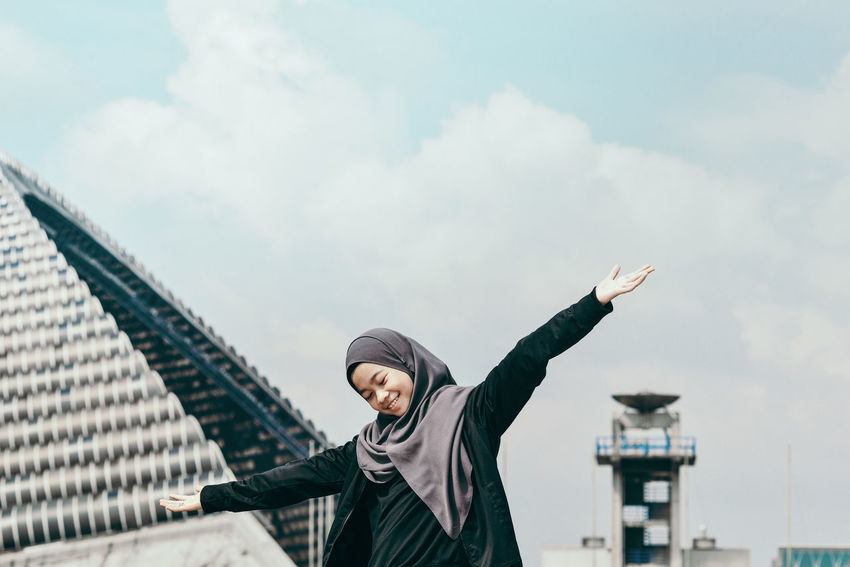 EyeEm Ready   Stadium Woman In Hijab Architecture Arms Spread Built Structure Leisure Activity One Person Outdoors Sky Young Women Stories From The City The Portraitist - 2018 EyeEm Awards