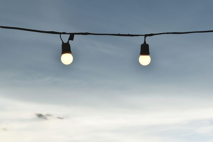 Low angle view of illuminated light bulb against sky