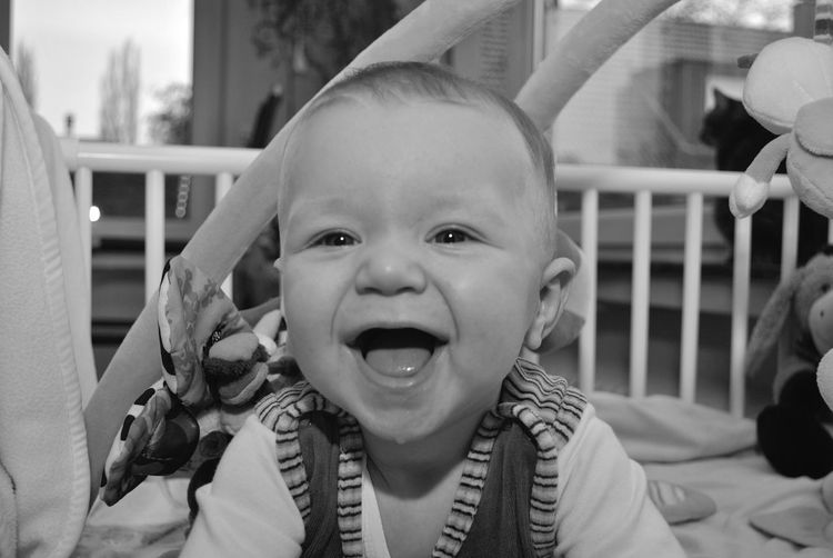 Close-up portrait of cheerful baby boy in crib at home