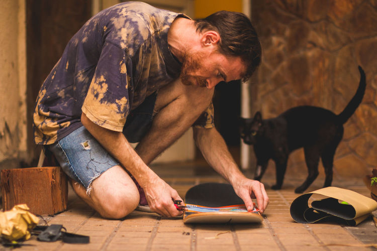 Man working with skateboard while kneeling on floor