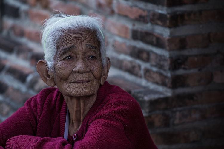 Senior Woman Looking Away Against Brick Wall