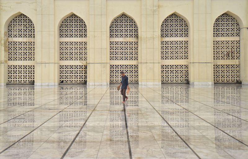 Full length of man walking on tiled floor