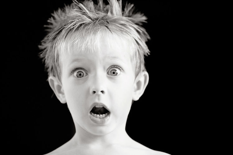 Portrait of shocked boy against black background
