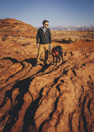 Full length of man with dog on rock