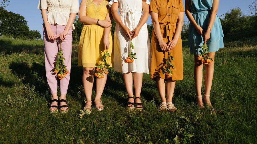 Low section of women standing on plants
