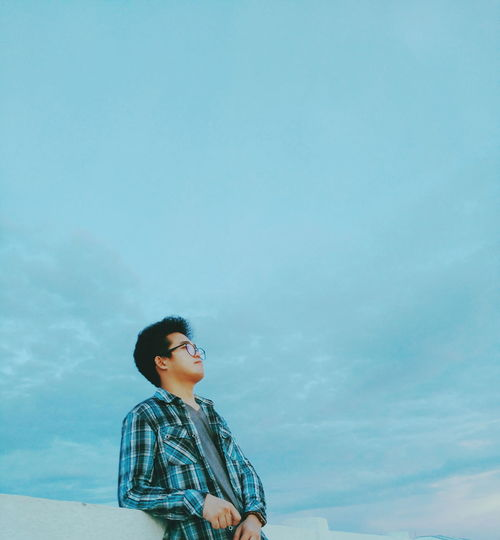 Thoughtful Young Man Looking Away While Standing Against Blue Sky