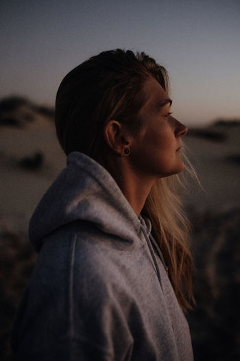 Side view of woman looking away against sky