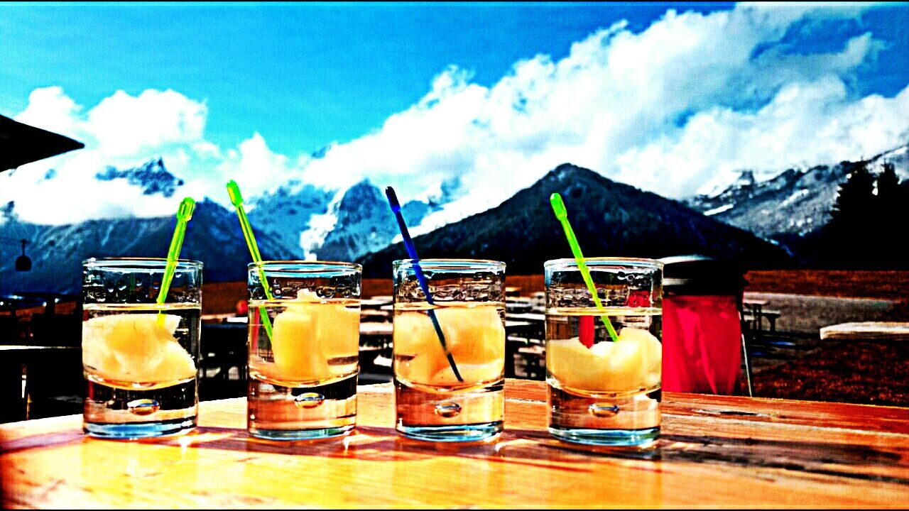 drink, food and drink, alcohol, refreshment, drinking glass, cocktail, drinking straw, freshness, no people, sky, tropical drink, focus on foreground, cold temperature, outdoors, table, mountain, day, close-up, tequila - drink, variation, fruit, shot glass, food, nature, mojito, liqueur