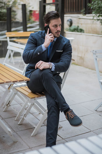 Businessman talking on mobile phone while sitting on chair in city