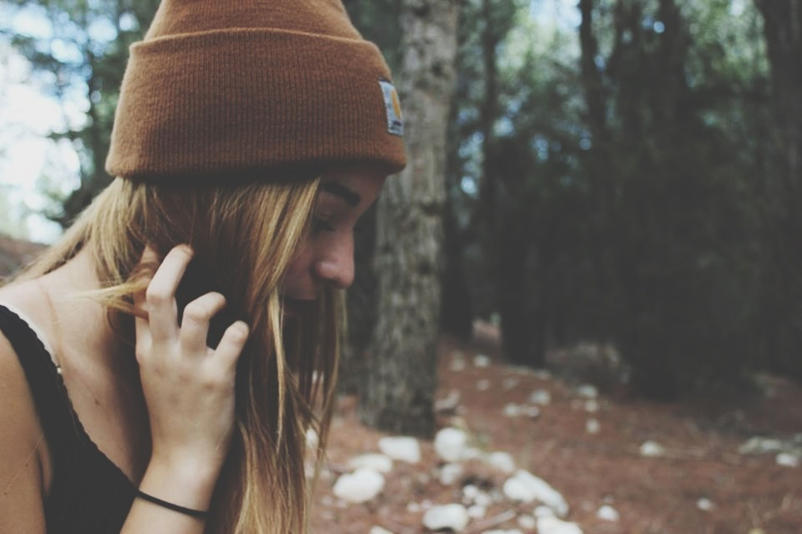 lifestyles, focus on foreground, leisure activity, tree, person, holding, close-up, casual clothing, young adult, young women, day, tree trunk, outdoors, park - man made space, rear view, hat, nature